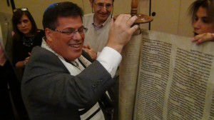 Cantor Neil Schnitzler unrolls a Holocaust surviving Torah scroll at Temple Emanuel